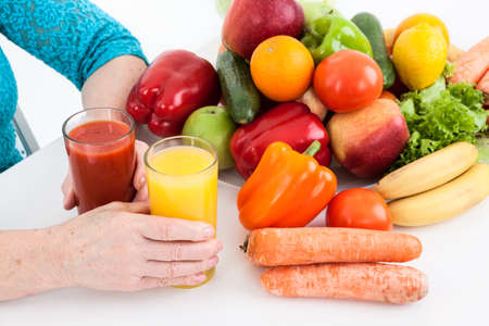 natural juices: Fresh ecological, natural products: vegetables, fruits and fresh juices are near arms of mature woman on a table