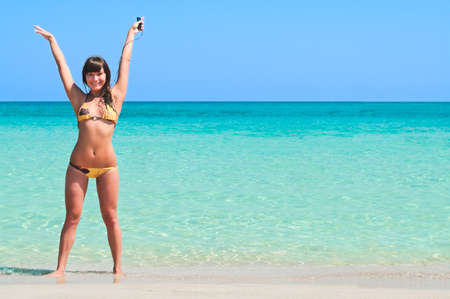 Young sexy girl standing on the sandy beach near the sea with hands up and listening to music on the player