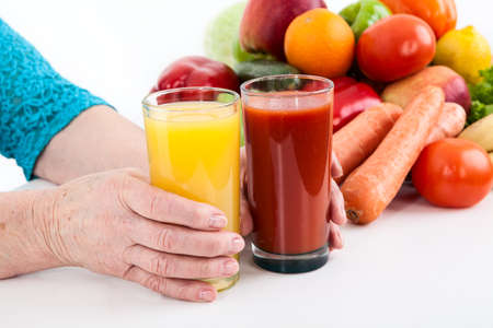 fruits juice: Women hands of an elderly woman holding two glasses of orange juice and tomato next to vegetables Stock Photo