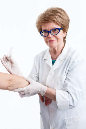 an inoculation: Elderly female nurse looking at camera while making an inoculation to the patient in hand, white background