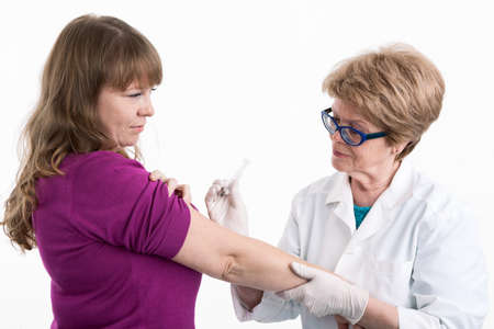 Senior Caucasian female nurse making vaccination to the adult patient in hand, white background