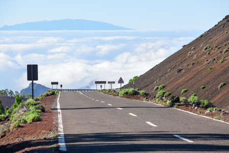 canaries: Mountain empty asphalt road going down in white clouds. Route to the Teide volcano, Tenerife, Canaries islands, Spain