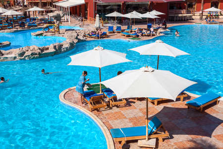 alf: HURGHADA, EGYPT - CIRCA NOV, 2015: Swimming pool with sun parasols is in the Egyptian hotel. The Alf Leila Wa Leila spa (1001 Nights) is one of the Pickalbatros