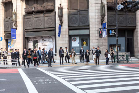 street light: TOKYO, JAPAN-Circa APR, 2013: Pedestrian intersection is in the on of central street of Tokyo. People are waiting for the green light. The central part with skyscrapers Editorial