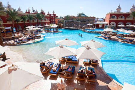 alf: HURGHADA, EGYPT - CIRCA NOV, 2015: View at the Egyptian hotel poolside with people sunbathing. The Alf Leila Wa Leila spa (1001 Nights) is one of the Pickalbatros