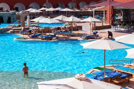 alf: HURGHADA, EGYPT - CIRCA NOV, 2015: Large swimming pool with people is in the Egyptian four stars hotel. The Alf Leila Wa Leila spa (1001 Nights) is one of the Pickalbatros