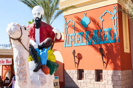 hotel chain: HURGHADA, EGYPT - CIRCA NOV, 2015: Statue of bedouin with camel is near the Egyptian hotel. The Alf Leila Wa Leila spa (1001 Nights) is one of the Pickalbatros chain spas in Hurgada resort