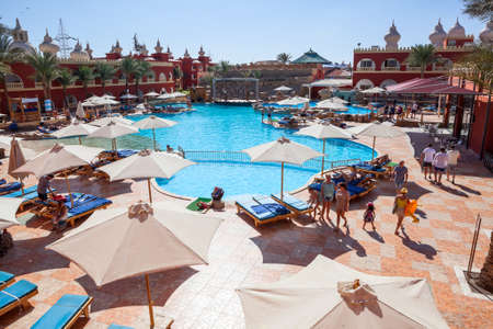 alf: HURGHADA, EGYPT - CIRCA NOV, 2015: Top view at swimming pool with people. Poolside is in the Egyptian four stars hotel. The Alf Leila Wa Leila spa (1001 Nights) is one of the Pickalbatros