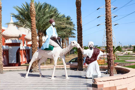 alf: HURGHADA, EGYPT - CIRCA NOV, 2015: Statues of bedouins with camel are near the Egyptian hotel. The Alf Leila Wa Leila spa (1001 Nights) is one of the Pickalbatros chain spas in Hurgada resort