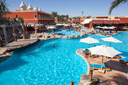 alf: HURGHADA, EGYPT - CIRCA NOV, 2015: People sunbath in the Egyptian hotel poolside. The Alf Leila Wa Leila spa (1001 Nights) is one of the Pickalbatros Editorial