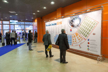 trade show: MOSCOW, RUSSIA - CIRCA NOV, 2015: People watch at information stand with map on the Metal-Expo'2015, the 21st International Industrial Exhibition in the All-Russia Exhibition Center