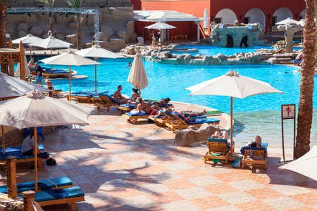 alf: HURGHADA, EGYPT - CIRCA NOV, 2015: Vacationers lay on the sun beds under parasols in the hotel poolside. The Alf Leila Wa Leila spa (1001 Nights) is one of the Pickalbatros