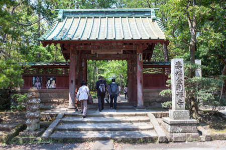 kanagawa: KAMAKURA, JAPAN-Circa APR, 2013: Tourists pass through the torii gate to the inner garden of Kaizo-ji temple. The Kaizo-ji shrine is in outskirts of Kamakura city, Kanagawa Prefecture