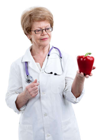 the cardiologist: An elder doctor cardiologist looking at red peppers in form of heart, isolated on white background Stock Photo