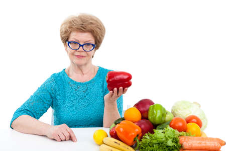 woman diet: Caucasian senior woman showing red sweet pepper in hand while sitting near fresh fruit and vegetables, isolated on white background Stock Photo