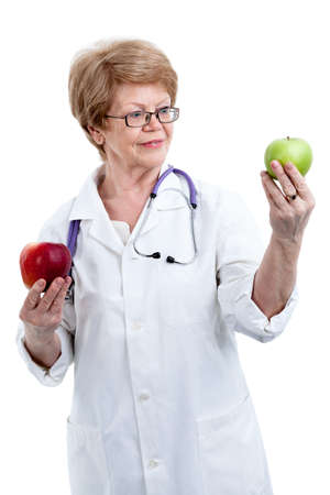 dietician: An elder doctor dietician showing green apple in one hand and holding red apple in other isolated on white background