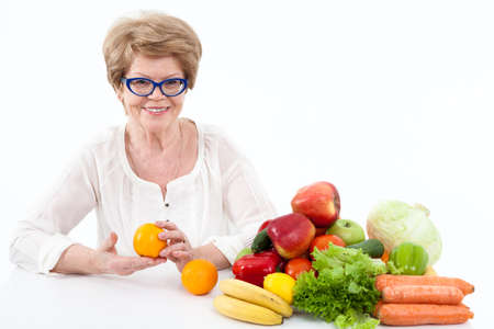 veggies: Smiling senior Caucasian woman holding hands two oranges, vegetables and fruits are on table, white background