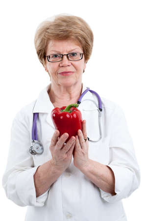 the cardiologist: An elder doctor cardiologist with red peppers in form of heart, isolated on white background