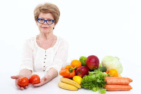 vegetables on white: Woman retirement age with two tomatoes in hands sitting near fresh fruit and vegetables, white background