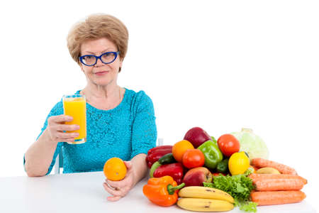 suggests: Joyful woman at the age suggests fresh orange juice in her hand, isolated on white background