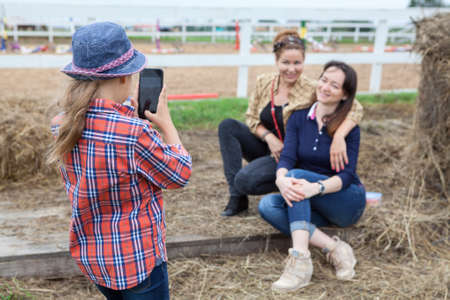 women sitting: Small girl photographing of two women sitting next to the hay on cellphone Stock Photo