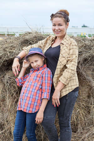 Caucasian mother and her little daughter wearing in shirts standing next to a stack of hay Stock Photo