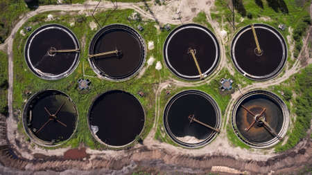 greywater: Circles of clarifiers on the earth and sedimentation tanks of city wastewater treatment plant. Aerial shot