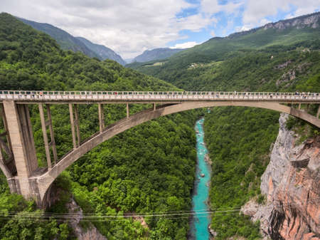 tara: The Durdevica concrete arch bridge. Cars driving and people riding on zip-line. Tara River canyon, Montenegro. Aerial side view from flying drone