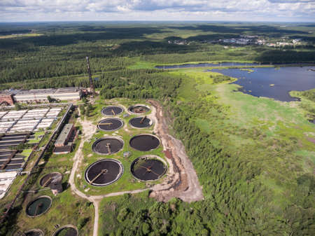 effluent: Primary settling tanks and clarifiers are on wastewater treatment plant in evergreen forest. Aerial view