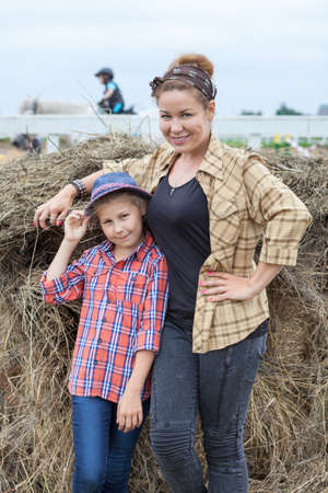Mom and daughter wearing in shirts standing next to a stack of hay