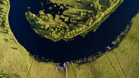 watercourse: Forest river watercourse in marsh. Wooden rowboats moored on the shore. Aerial view. Northern Karelia, Russia