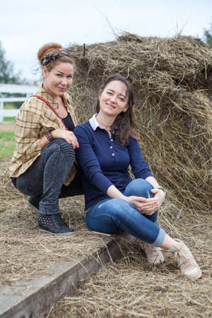 Two beautiful women a girlfriends sitting beside a stack of hay Stock Photo