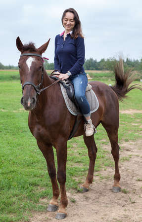 Pretty young woman sitting on a horse while riding Imagens