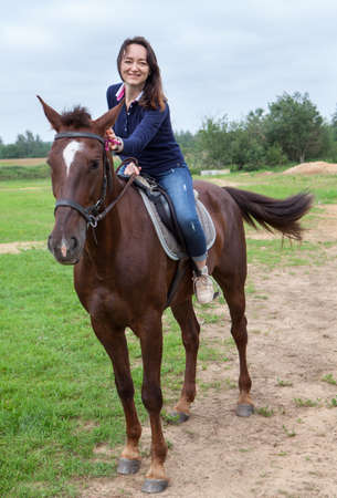 Joyful young woman touching her chestnut horse while riding on field photo