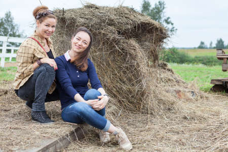 Two girlfriends sitting beside a stack of hay, copyspace photo