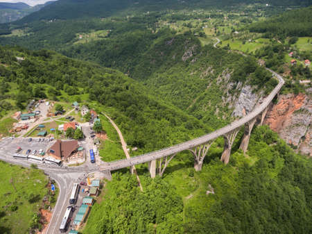 tara: Long concrete arch bridge over the Tara River. Durdevica bridge across rock canyon. Aerial view of beautiful nature of national park. Montenegro, Europe Stock Photo