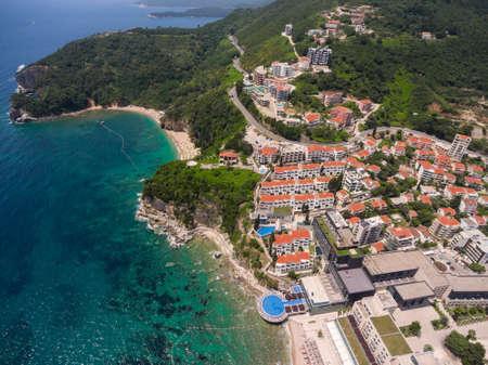 costal: Costal asphalt road passing through the Budva city, over the Mogran beach. Aerial shot. Montenegro Stock Photo