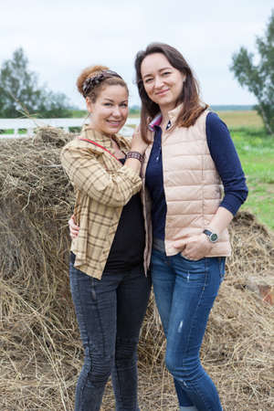 Two joyful women standing together on countryside with haystack on background photo