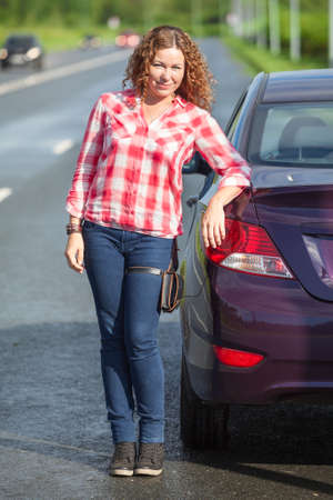 joyous: Young woman wearing jeans and red shirt stands near own car at highway Stock Photo
