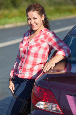 Attractive young female driver with own car, looking at camera