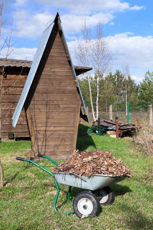 Wooden wc and wheelbarrow on rural courtyard Stock Photo