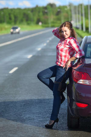 red plaid: Joyful woman in red plaid shirt and on high heel posing near car on the roadside, full length