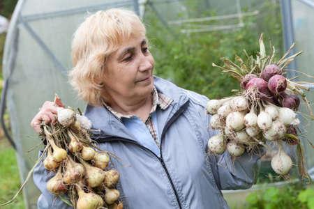 garlic: La mujer sostiene un manojo de cebollas rojas y blancas en sus manos, de pie cerca del invernadero Foto de archivo