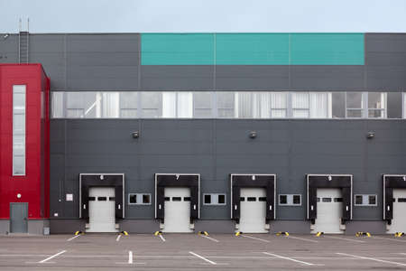 Modern truck loading bays with overhead doors are in an industrial warehouse. Empty area, close gates Stock Photo