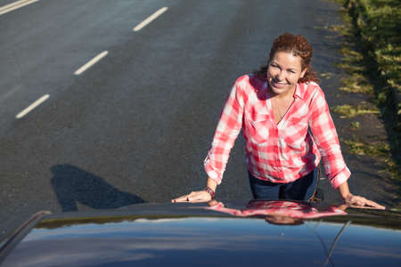 capote: Young woman a driver standing near closed car hood on the asphalt road