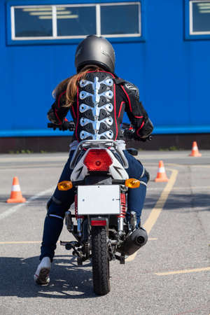 motociclista: Young woman motorcyclist has driving lesson on motordrome, rear view