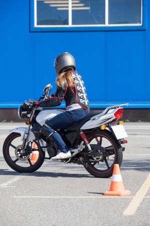 Vrouw beginner doet oefening rond kegels op de motor in vaardigheidstraining motordrome. Russische chauffeur scholen Stockfoto