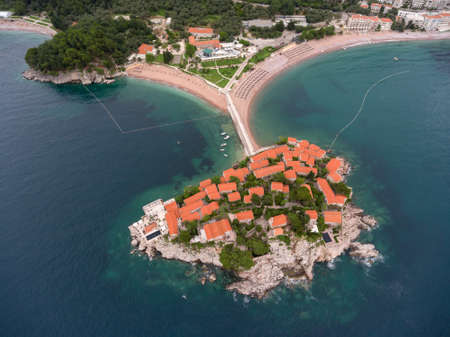 sea of houses: Houses of luxury hotel of Villa Milocer (Aman Resorts) are on the Sveti Stefan rocky island. Aerial view from Adriatic sea. Montenegro Stock Photo