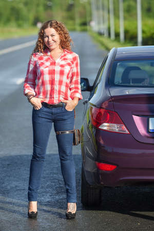 joyous: Caucasian joyful woman on high heel stands with hands in jeans pockets near her car on the roadside