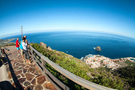 steep: GARACHICO, TENERIFE, SPAIN-CIRCA JAN, 2016: People stand on the Mirador (viewpoint) and look at beautiful view of cape with Garachico town. Northern part of Tenerife island. Wide angle Editorial
